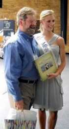 Miss Michigan 2009, Nicole Blaszczyk, accepts a 'Pure Michigan' book from a staff member at the New Buffalo Welcome Center, the nation's first Highway Travel Information Center, during a celebration of the center's 75th anniversary.  (Tribune Photo/DOUGLAS FARMER)
